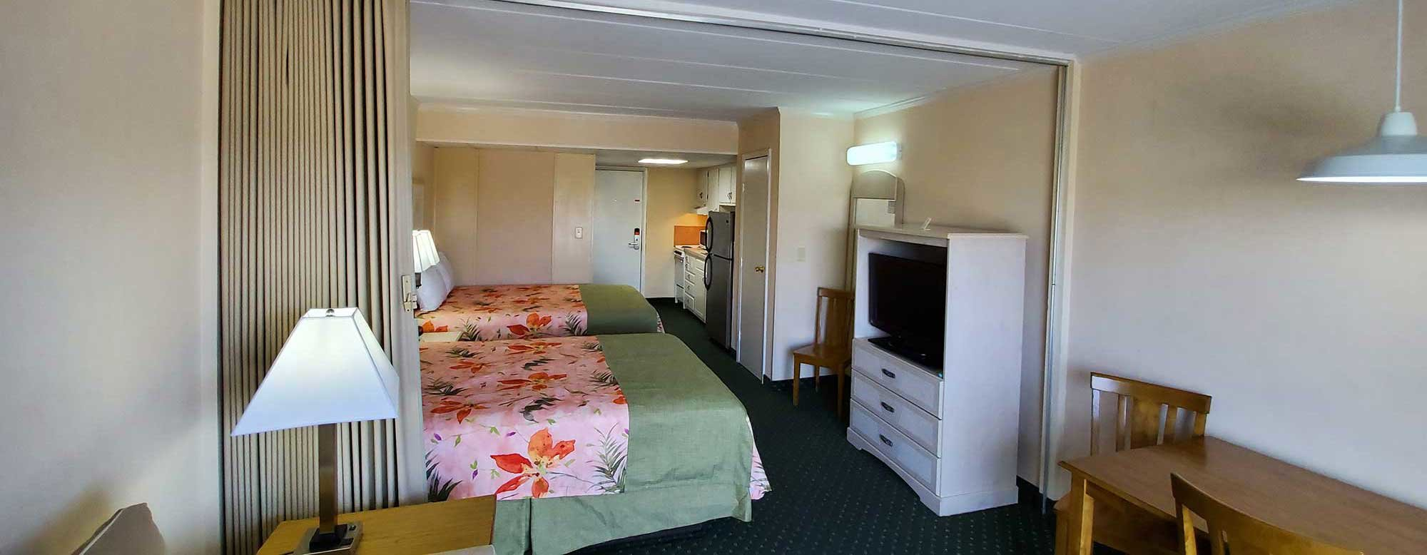 Efficiency Room at the Sea Hawk Motel with two queen beds, TV, table and kitchen