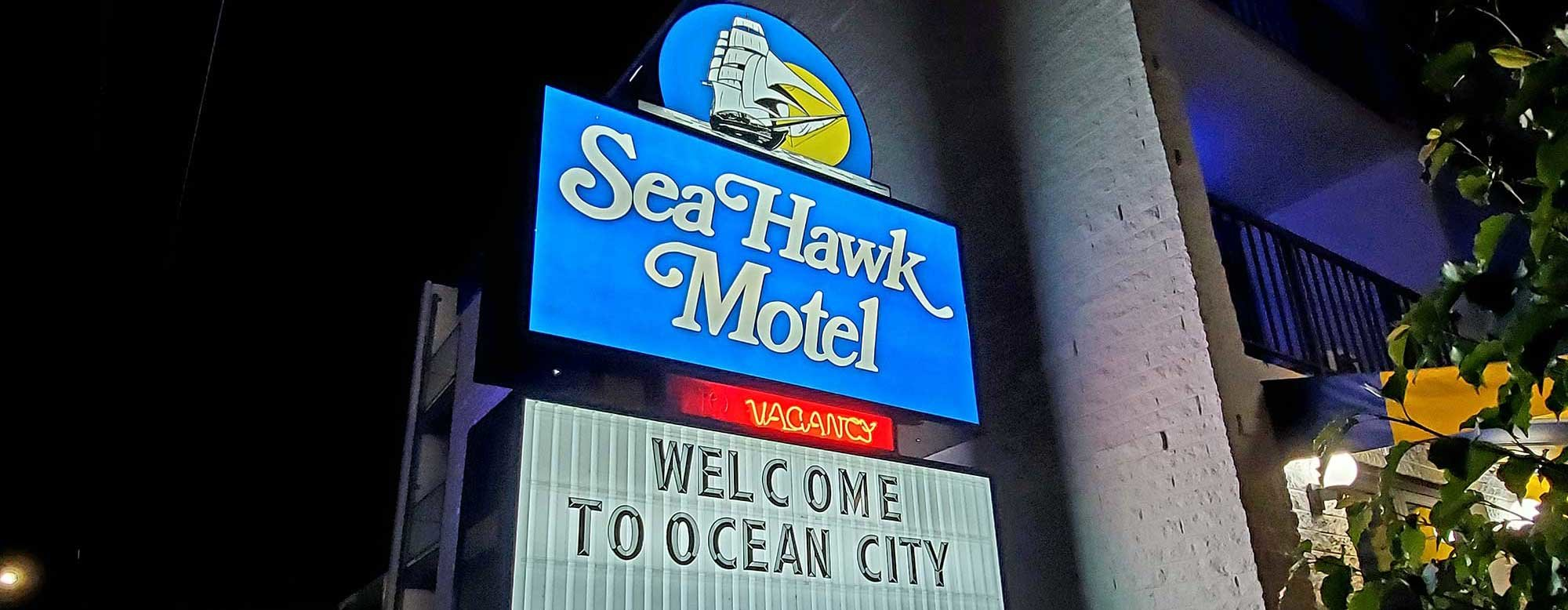 Sea Hawk motel sign lit in the evening